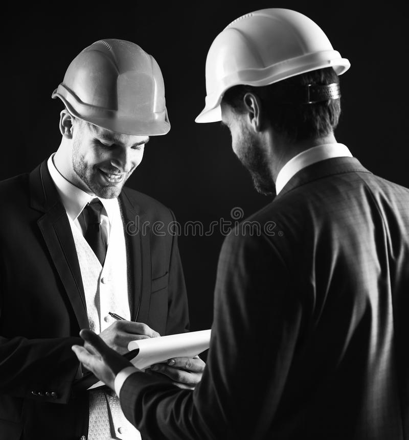 Construction, architecture, work, job concept. Engineers with smiling faces discuss project. Businessman and happy architect with architectural project. Boss stock images