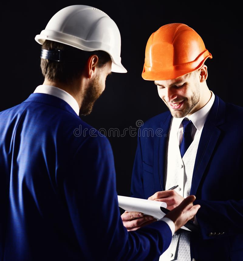 Construction, architecture, work, job concept. Engineers with smiling faces discuss project. Businessman and happy. Architect with architectural project. Boss stock photo