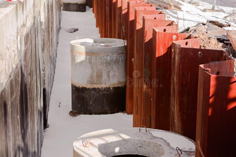 Construction avec des anneaux concrets et une barrière de rouge en métal photos stock