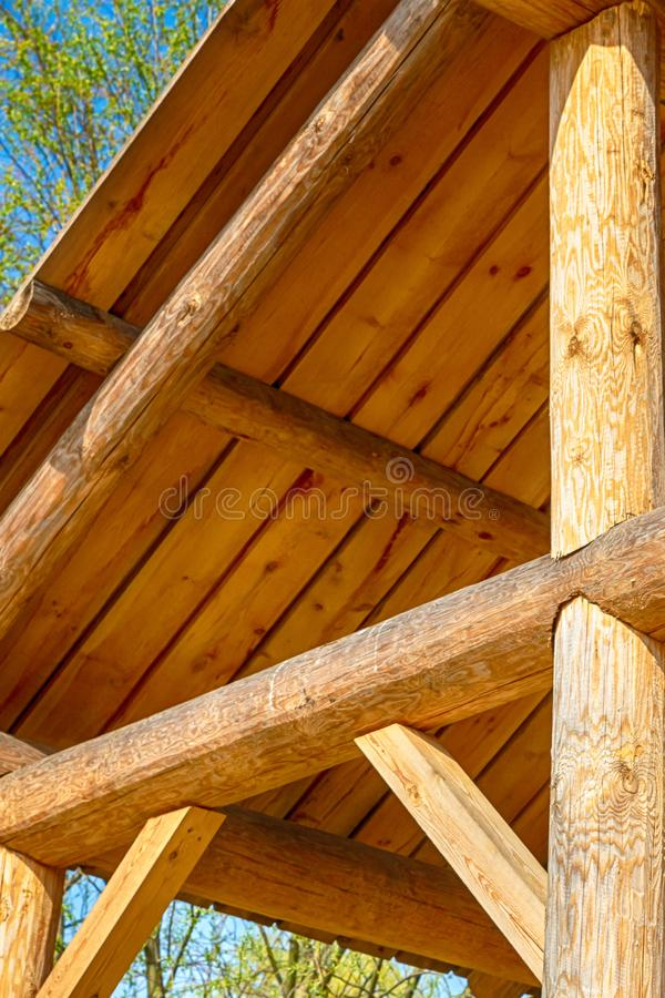Construction beam part wooden roof, traditional rustic construction close-up on sky background stock images