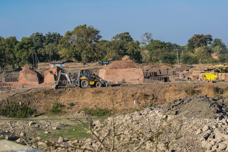 Brick kiln and Brick Manufacturing Site India. Construction Brick kiln and Brick Manufacturing Site India showing a Loader Backhoe Digger and Bricks. near the royalty free stock photography