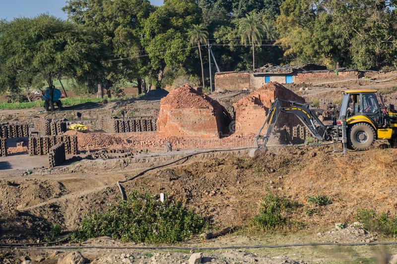 Brick kiln and Brick Manufacturing Site India. Construction Brick kiln and Brick Manufacturing Site India showing a Loader Backhoe Digger and Bricks. near the stock image