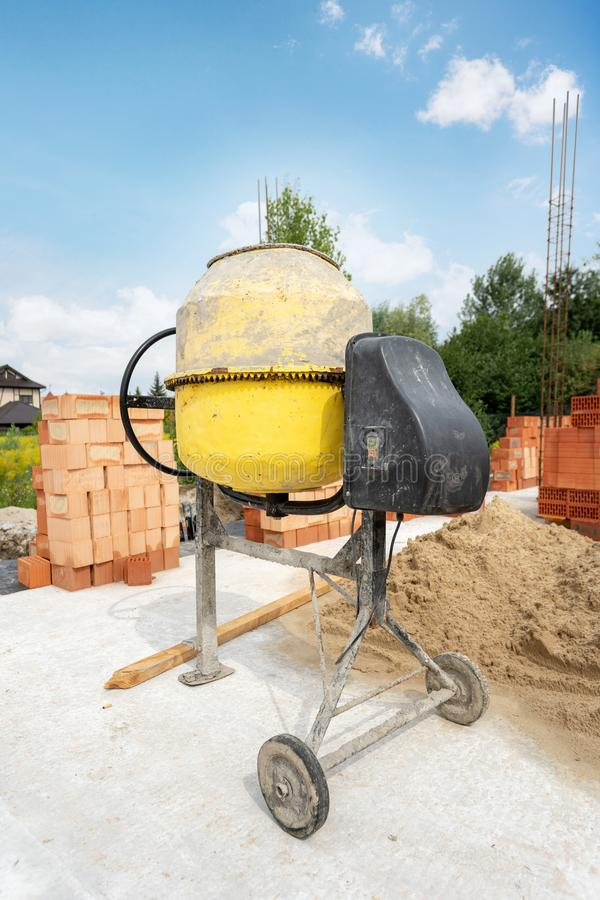 Construction of brick new home or house. Vertical day lite photo of old yellow professional concentrate mixer stand outside on the. Foundation of an unfinished royalty free stock photography