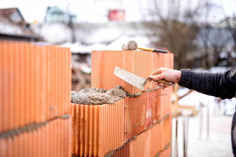 Construction bricklayer worker building walls with fresh bricks and tools royalty free stock images