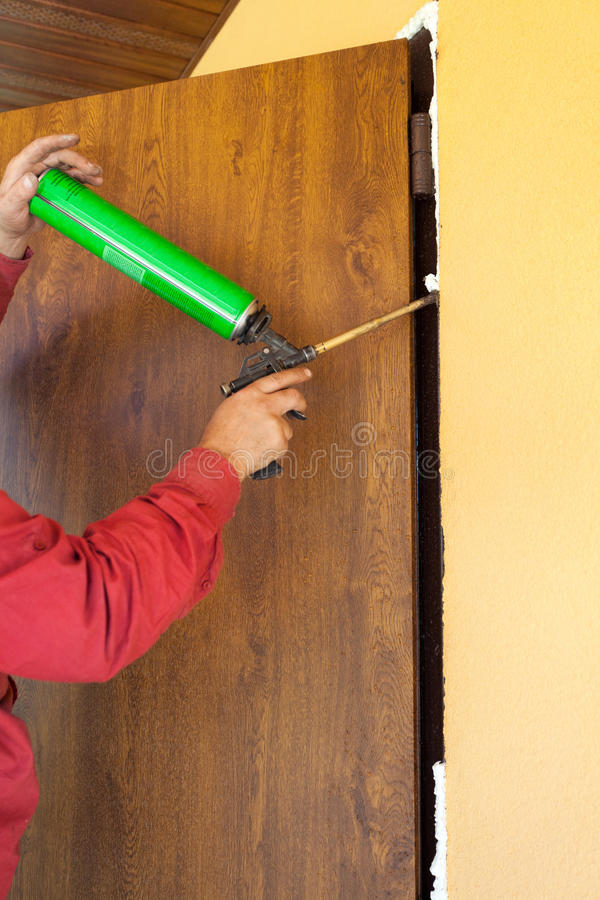 Construction builder works with polyurethane foam during frame insulation at door installation. royalty free stock images