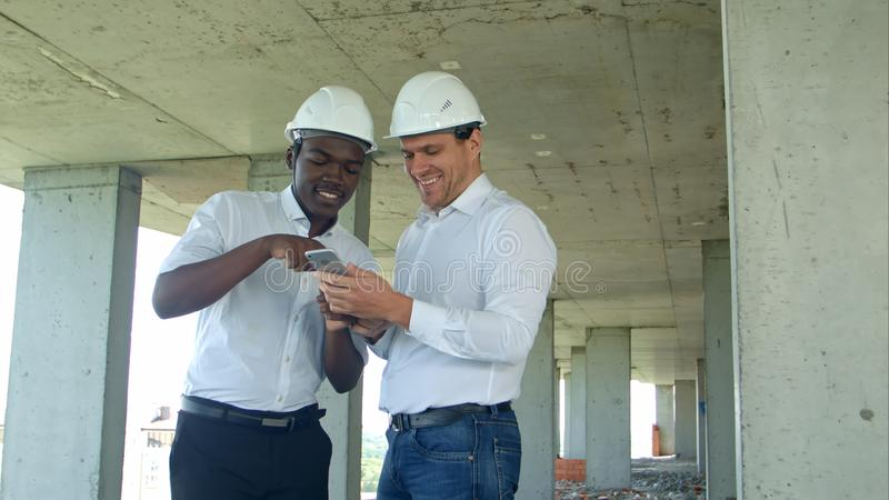 Construction builders smiling while using smartphone at site royalty free stock image