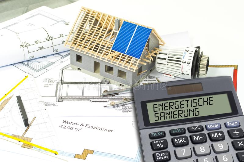 Construction or building plan with bricks and calculator showing the german word for energetic renovation - energetische sanierung stock photo