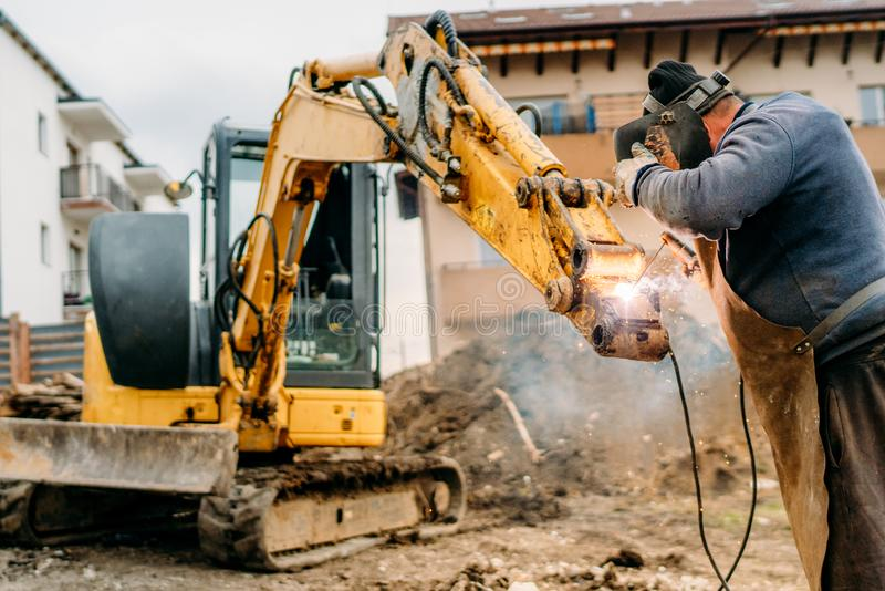 Construction building site, broken excavator and professional welder royalty free stock images