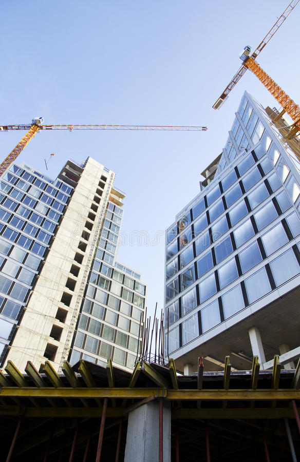 Construction of buildings. Buildings construction process with cranes stock image
