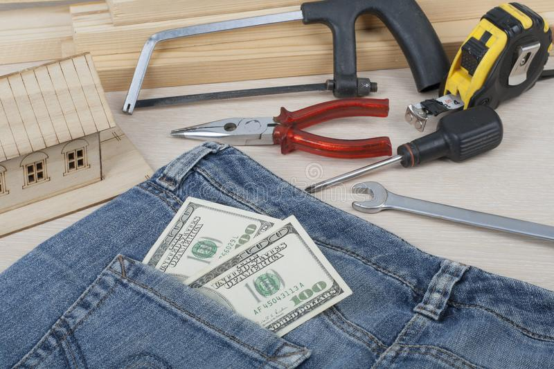 Construction and business concept. Different working tools, dollars in the pocket of jeans on wooden background. royalty free stock photos