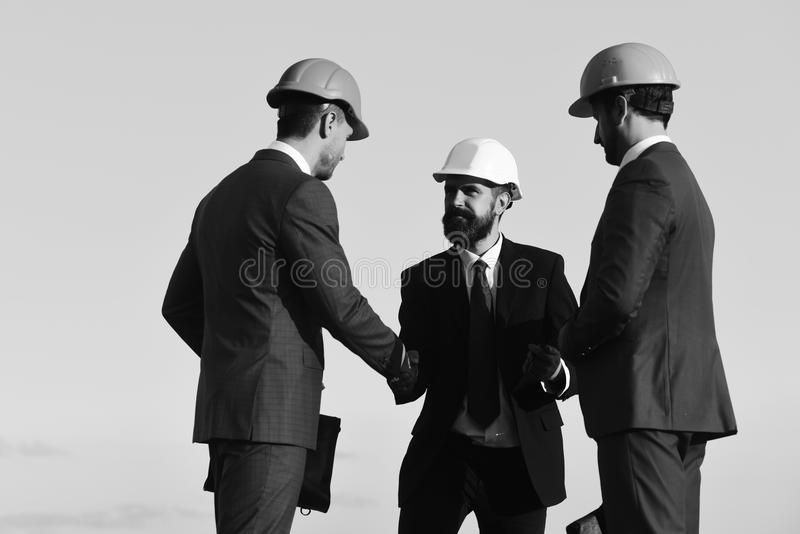 Construction and business concept. Leaders hold clip folder and shake hands. royalty free stock photography