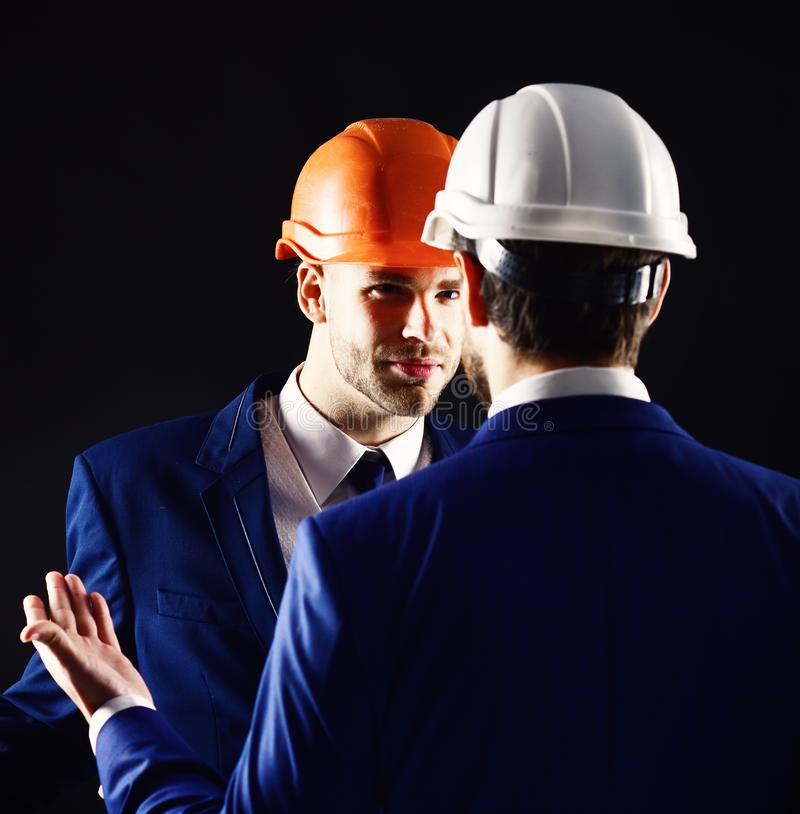 Construction business concept. Technical architect talks to project manager with serious face. Engineers with calm faces stock photography