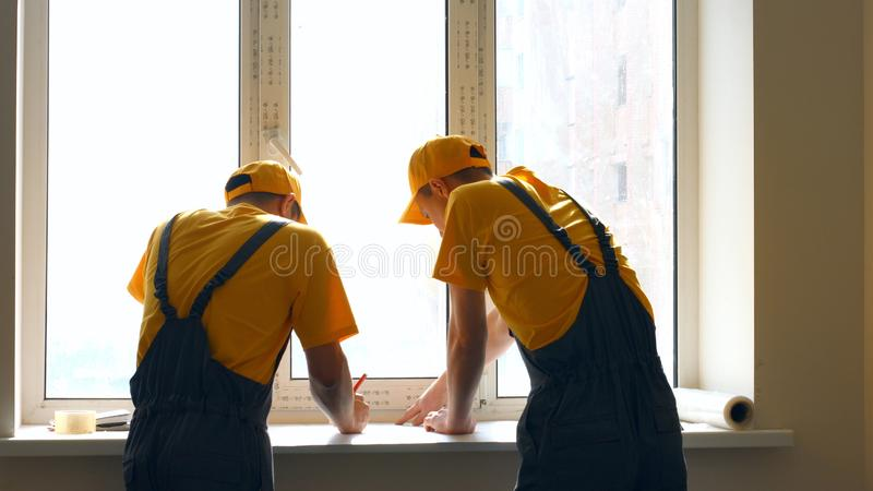 Construction co-workers discussing work plan. Project discussion at construction site stock photography