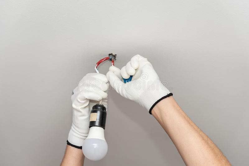 Construction concept. Hands of a worker in white gloves perform work with electricity in the house stock photos