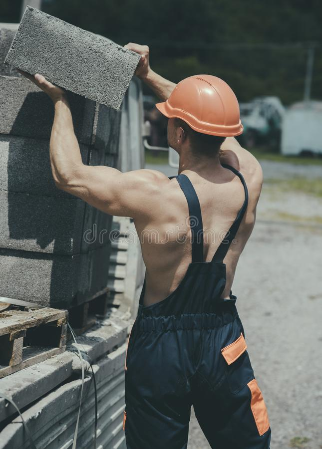 Construction concept. Man carry bricks for construction works. Builder unload truck on construction site. Construction royalty free stock images