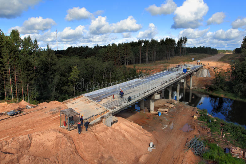 Construction of a concrete bridge across the river stream stock photo