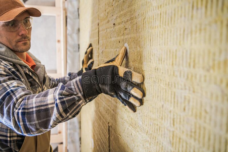 House Wool Insulation. Construction Contractor Worker Finishing Mineral Wool Insulation Installing stock images