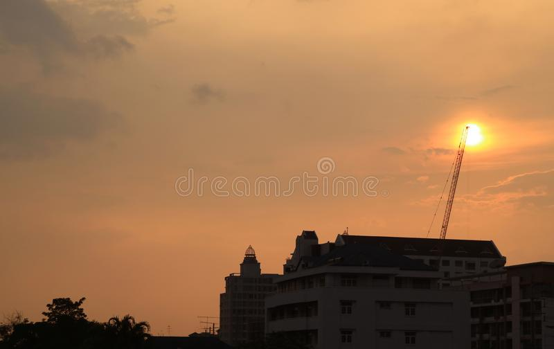 Construction crane against dazzling setting sun stock photography