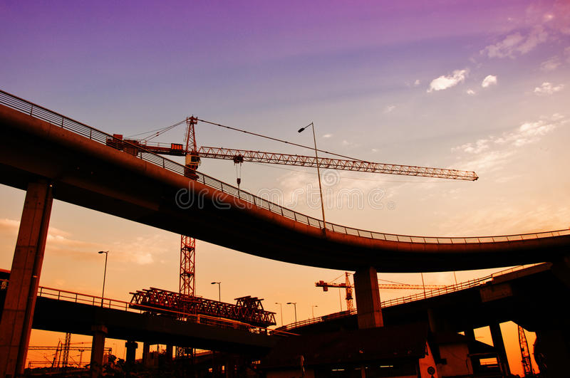 Construction crane in dusk. Silhouettes of construction crane and a bridge in dusk against the colorful sky royalty free stock image