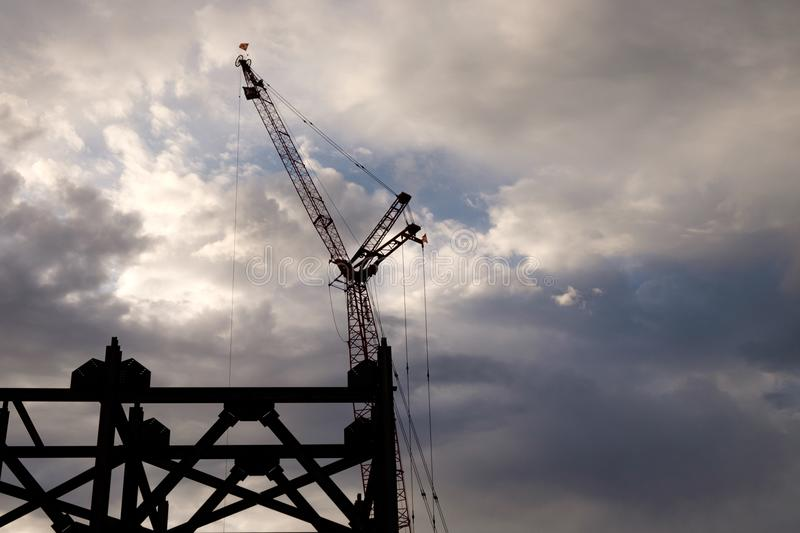 Construction crane early on a cloudy morning stock photography
