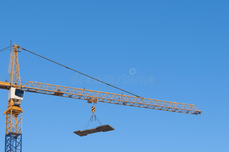 Construction crane hanging load. Construction crane with hanging load at building site. Arlanda sweden royalty free stock images