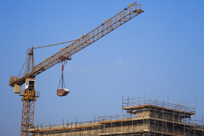 Construction crane lifting cargo with clear blue sky stock image