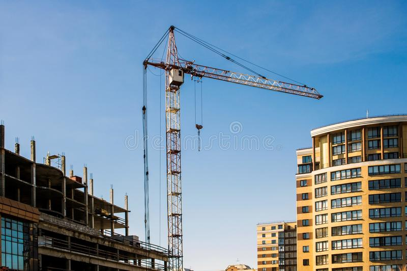 The construction crane between the new house and the unfinished house stock photography