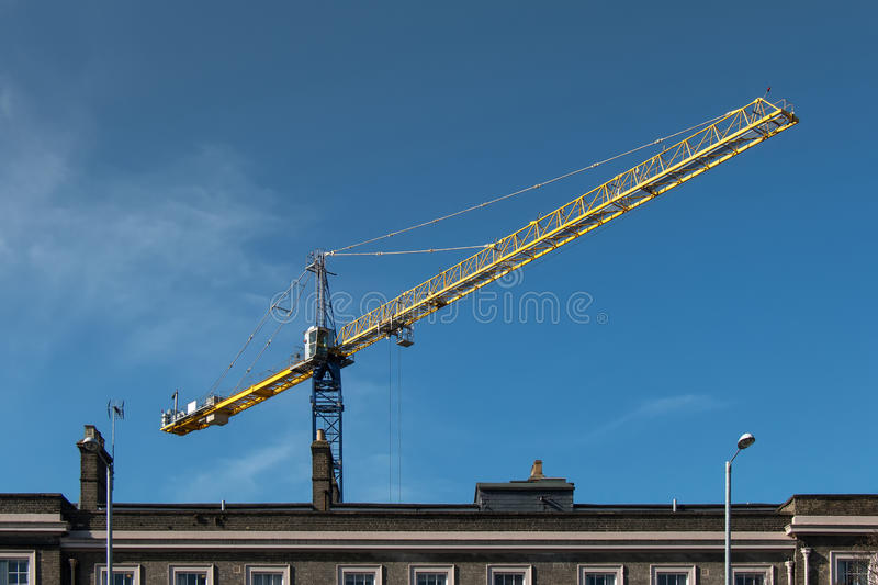 Construction Crane. Site behind a Building stock photography