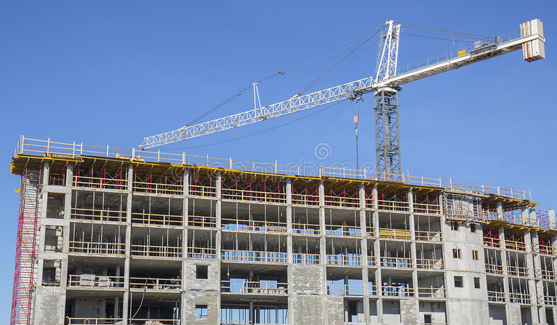 Construction Crane On Site. Construction crane on top of a new building being built royalty free stock images