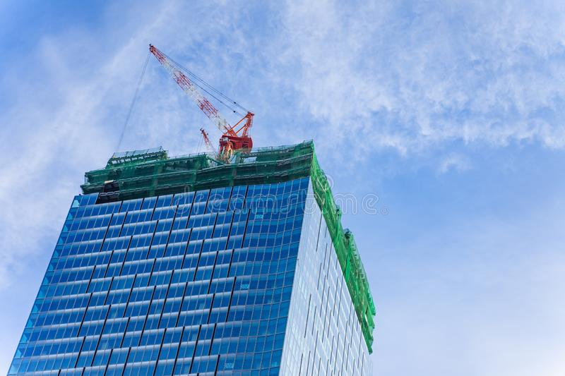 Construction crane on top of tower working to build high skycrapper office building in the development city, cloud blue sky. Construction crane on top of tower stock photo