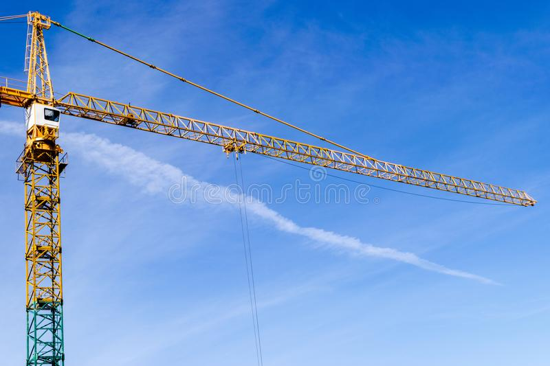 Construction crane tower on background of blue sky. Crane and building working progress. Yellow lifting faucet. Empty Space. For text. Construction concept stock image