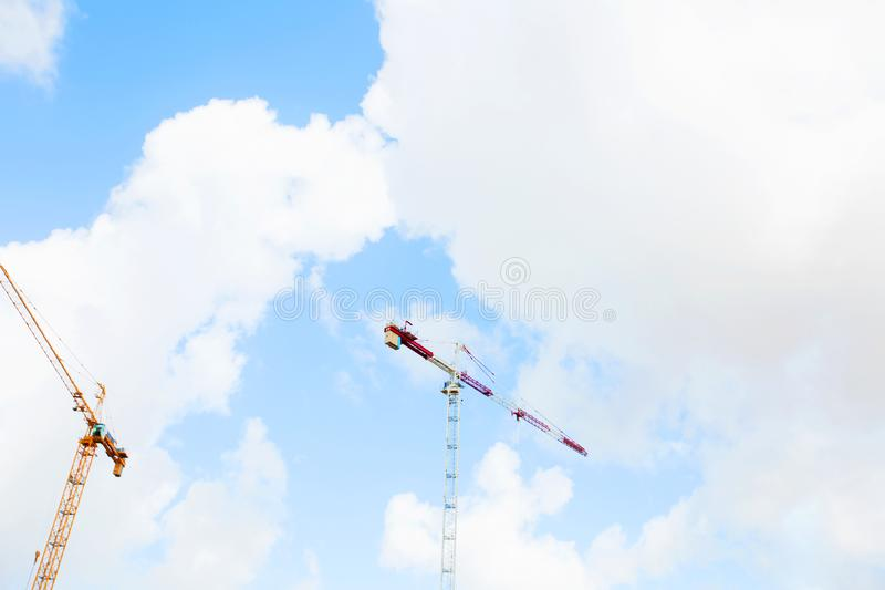 Construction crane tower on background of blue sky. Crane and building working progress on construction site. Lifting faucet. Construction crane tower on royalty free stock photography