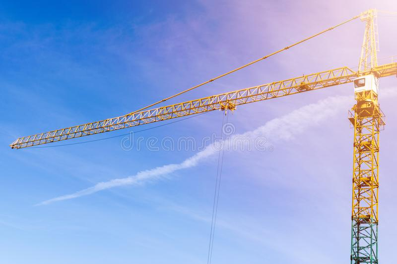 Construction crane tower on background of blue sky. Crane and building working progress. Yellow lifting faucet. Empty Space for te. Xt. Construction concept stock photos