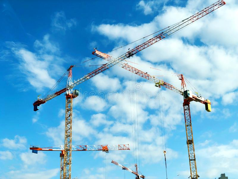 Construction crane tower on blue sky background. Crane and building working progress. Yellow lifting faucet. Construction crane tower on blue sky background stock photo