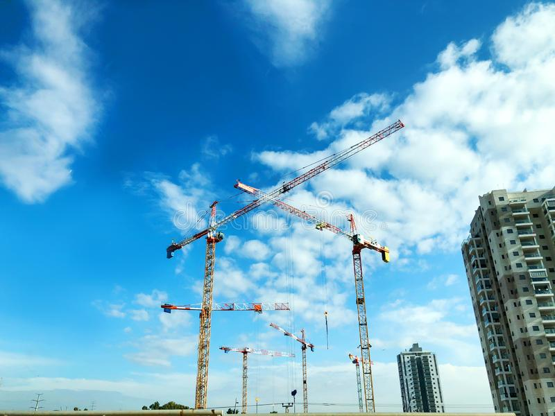 Construction crane tower on blue sky background. Crane and building working progress. Yellow lifting faucet. Construction crane tower on blue sky background stock images