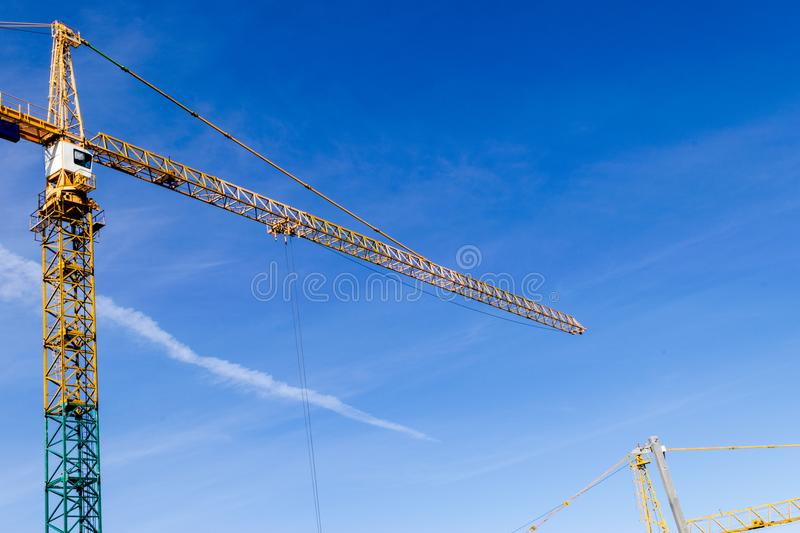 Construction crane tower on blue sky background. Crane and building working progress. Yellow lifting faucet. Empty Space for text. Construction concept. Site royalty free stock photos
