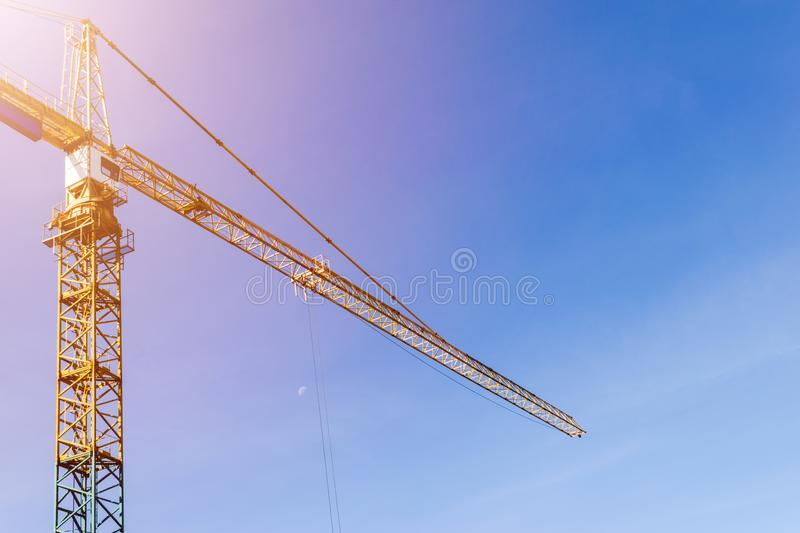 Construction crane tower on blue sky background. Crane and building working progress. Yellow lifting faucet. Empty Space for text. Construction concept. Site stock photo