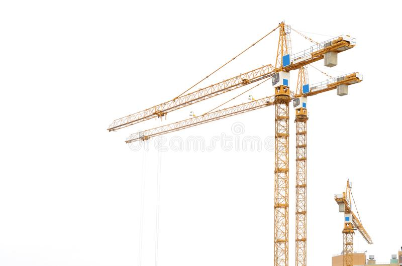 Construction crane on white background. It is used to lift loads at the construction site stock images