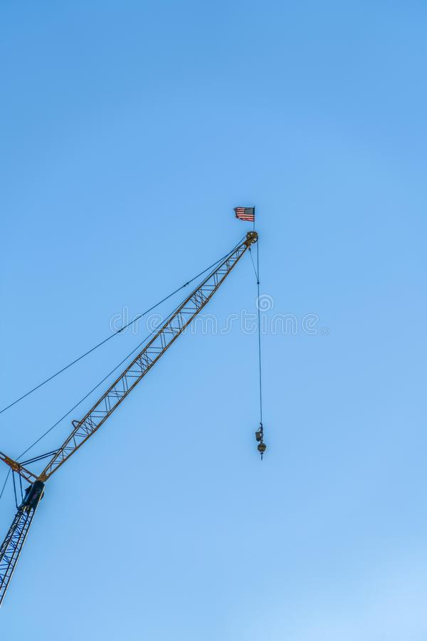 Construction crane with wires and American flag isolated against clear blue sky. The machine is used for lifting, lowering, and transporting heavy materials stock images