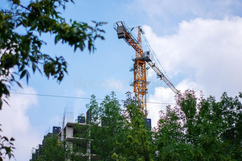 A construction crane works against a background of blue sky and green trees. The construction of a high-rise building with an royalty free stock photo