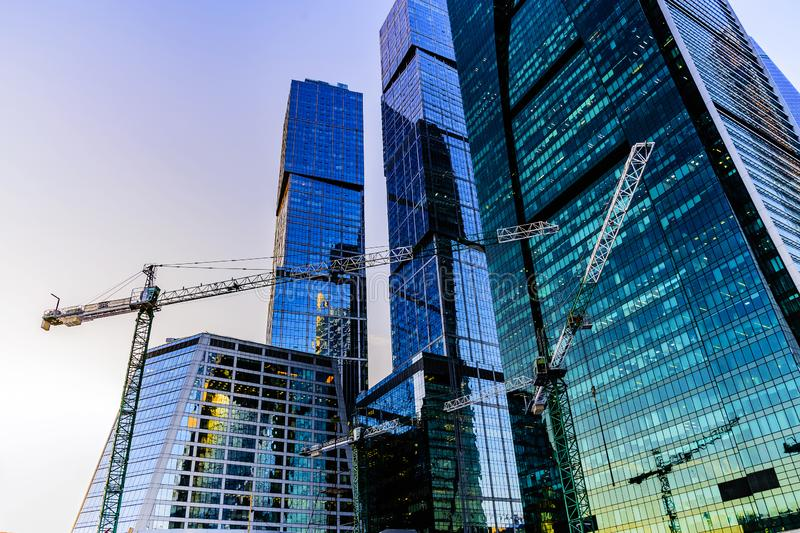 Construction cranes against the background of the international business center `Moscow City` on a winter evening. royalty free stock photo