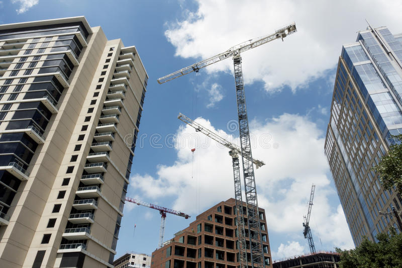 Construction cranes building new buildings in a downtown area. Building cranes transporting concrete and tools to buildings being constructed in a downtown area royalty free stock photos