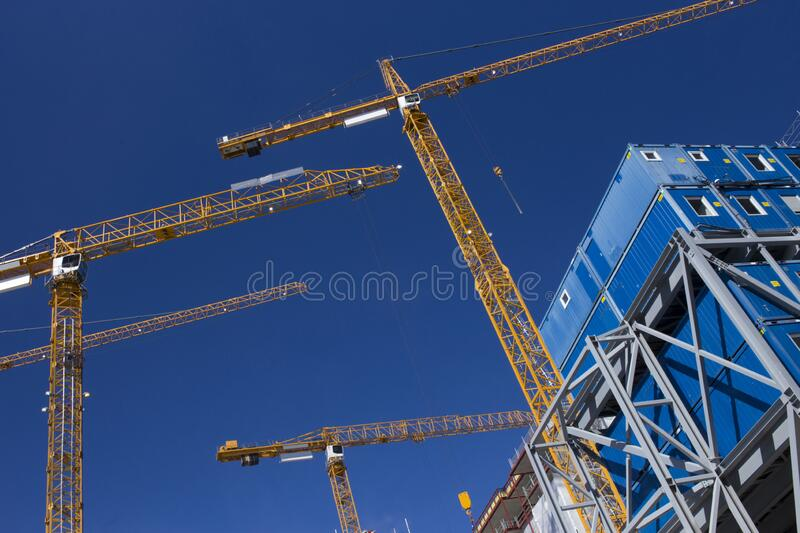 Construction cranes building a skyscraper stock photography