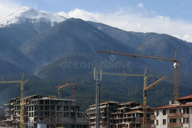 Construction cranes on a mountain in heavy constructions of hotels ruin the nature. Dangerous climate changes. Great pollution of stock photos