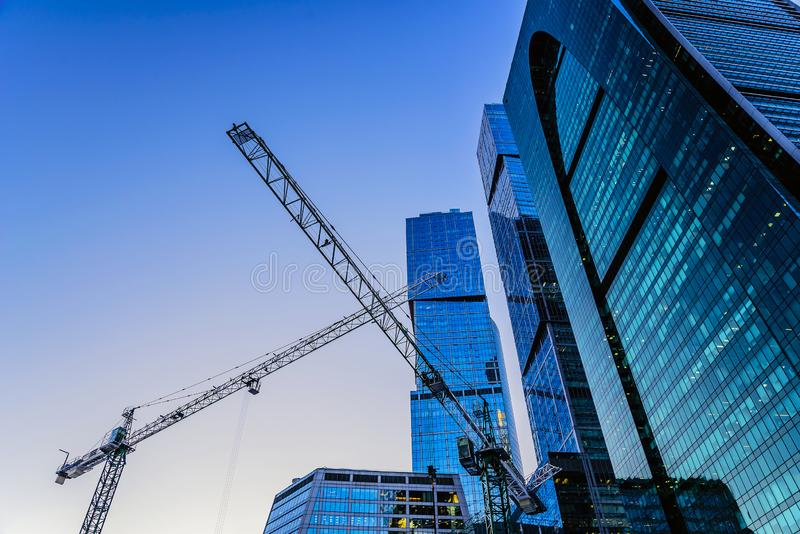 Construction cranes and towers of the Moscow-City international business center in the winter evening against the blue sky. Moscow royalty free stock photo