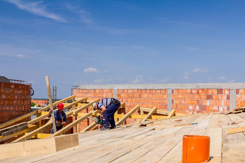 Construction crew of carpenters is working on the new roof royalty free stock image