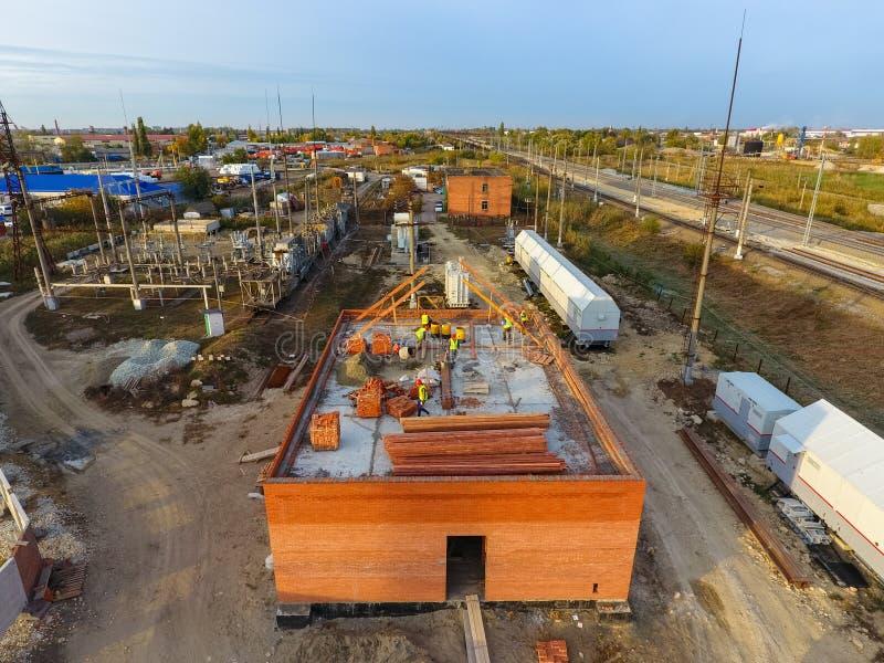 Construction d'un immeuble de brique Installation du toit Travaux de construction photographie stock libre de droits