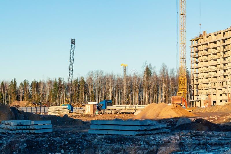 Construction d'un nouveau bâtiment à plusiers étages entouré par des forêts Grues de construction contre le ciel bleu photos stock