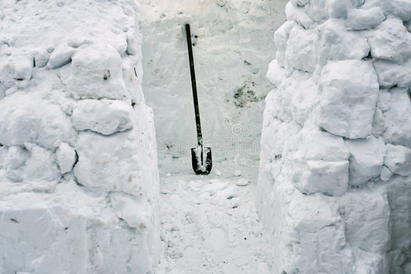 Construction d'une maison de neige des briques de neige utilisant une pelle photographie stock