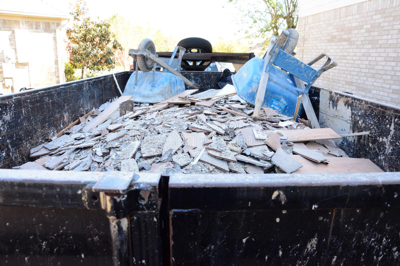 Construction Debris Pile. Construction debris in a pile outside of home remodel with flooring tiles hauled away in trailer royalty free stock images